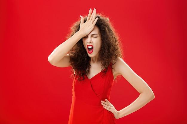 Donna incazzata con gente stupida. femmina caucasica adulta smemorata irritata con capelli ricci in vestito elegante rosso che perfora la fronte con la palma che chiude gli occhi e giura che ricorda cosa importante.