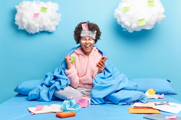Woman being on self isolation works distantly stays in bed wears slumber suit and sleepmask uses smartphone for online communication