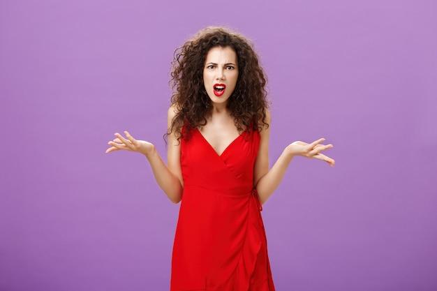パーティー中に彼女と別れるショックを受けた男にショックを受けた女性。無知で疑わしいポーズで手のひらを広げて肩をすくめる夜の化粧をした赤いドレスを着た心配して怒り狂った格好良い女性。