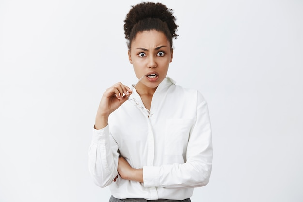 Woman being shocked listening to terrible news on tv. portrait of shook displeased and questioned woman in shirt, biting rim of glasses staring with popped eyes and frowning from stupor