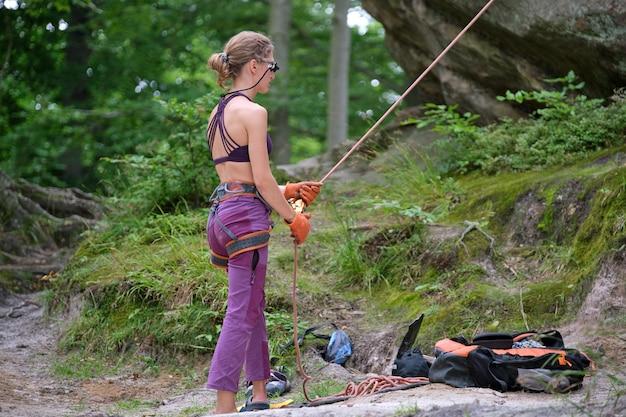 女性はビレイ装置とロープでパートナークライマーをビレイします。ロック登山のセキュリティのための機器を保持しているクライマーのヘルパー。