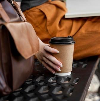 Woman on bench grabbing coffee