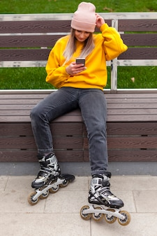 Woman on bench looking at phone while wearing roller blades
