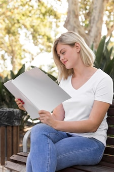 Woman on bench outdoors reading book
