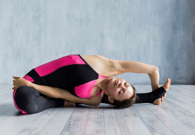 Woman bending over her shoulder while stretching her foot