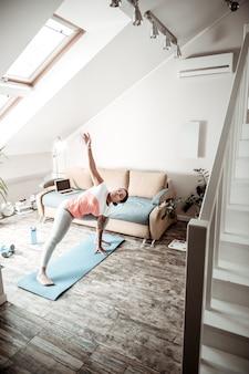 여자 굽힘 허리. 높은 천장과 다락방 창문이있는 넓은 아파트에서 스포츠를하는 적극적인 여성