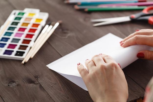 折り紙のために一枚の紙を曲げる女性