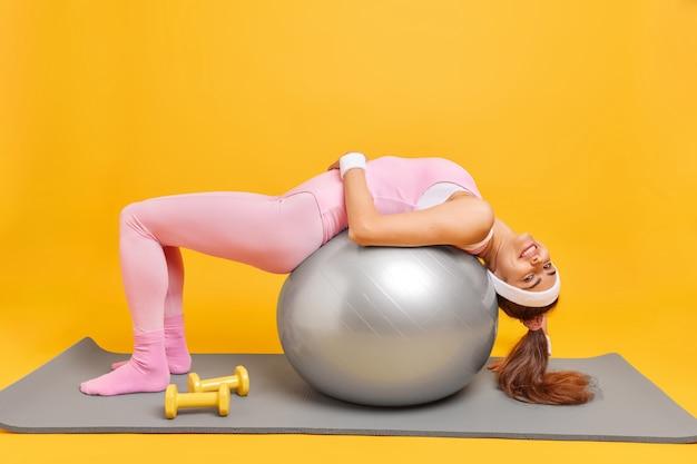 Женщина наклоняется на фитнес-мяче занимается дома, держит форму, одетая в спортивную одежду, повязка на голову, браслеты, позирует на коврике на желтом