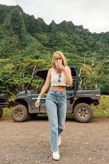 ハワイのジープ車の横にある女性