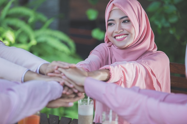 Woman best friends putting hands together at cafe