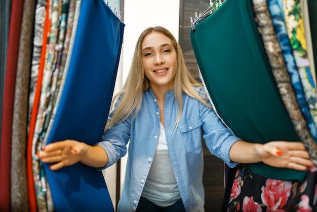 Женщина между тканью в текстильном магазине. швея выбирает материал для шитья, портниха в магазине, портниха