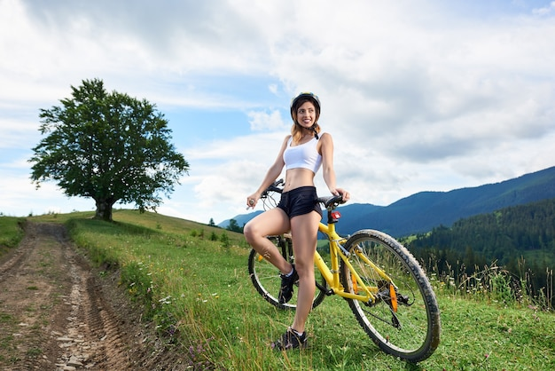 Woman bicyclist cycling bicycle in the mountains