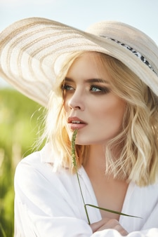 Woman in a big hat and a long white dress is sitting in the grass in a field. blonde woman in the sun in a light dress. woman resting and dreaming, perfect summer makeup on her face