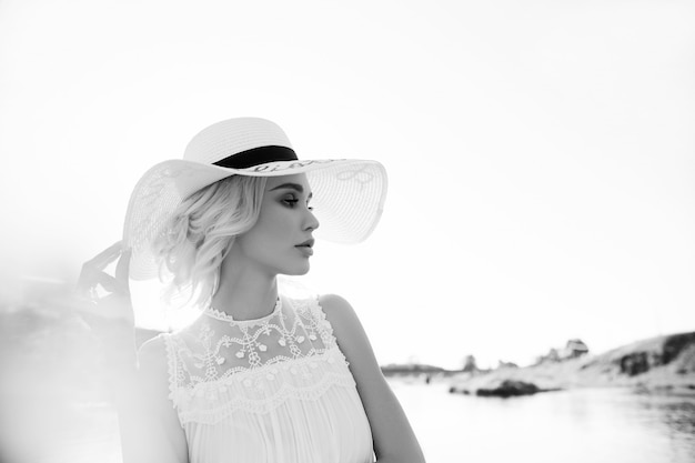 Woman in a big white hat stands near the sea, a blonde in a hat looking at the lake, summer vacation travel and vacation. sun rays at sunset
