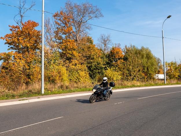 田舎の秋の道の交通で黒いバイクに乗った女性バイカー
