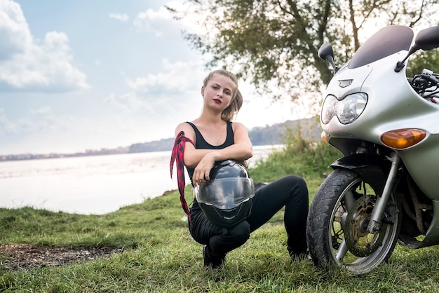 Woman biker sitting near motorcycle with helmet in her arms