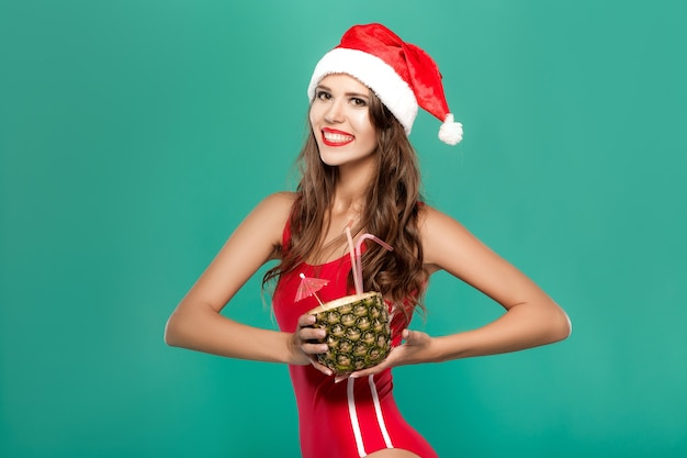 Woman in bikini drinks summer cocktail in pineapple