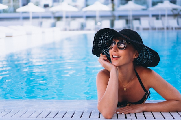 Woman in bikini in hat by the pool