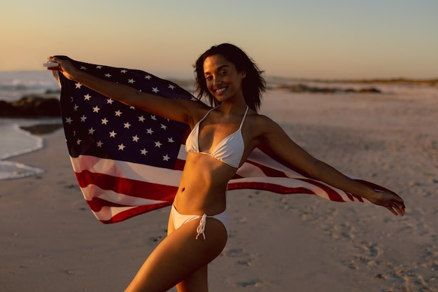 Woman in bikini holding an american flag on the beach