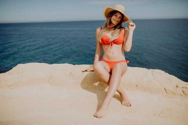 La donna in bikini è seduta sul bordo di una montagna
