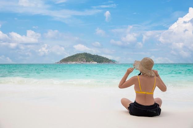熱帯の海を眺めるビーチで、太陽の麦わら帽子をかぶって後ろからリラックスする女性のビキニ、夏休み旅行のコンセプト