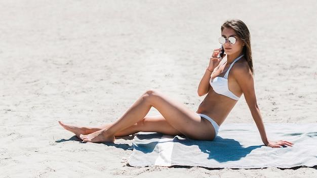Woman in bikini speaking on phone on beach
