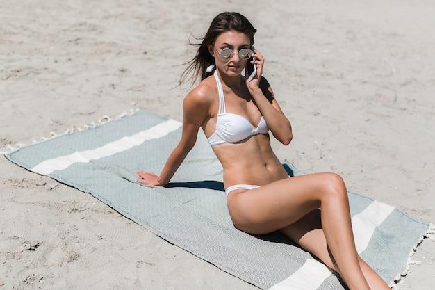 Woman in bikini speaking on phone