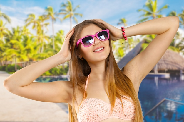 Woman in bikini and sunglasses isolated