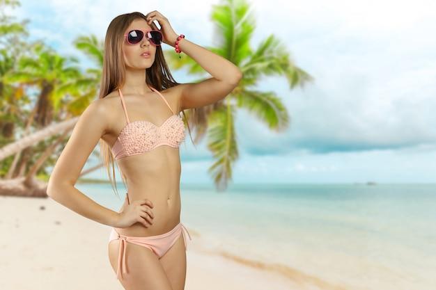 Woman in bikini and sunglasses isolated