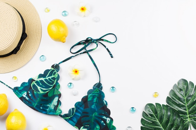 Woman bikini swimsuit with straw hat, flowers and fruits, copy space. travel concept