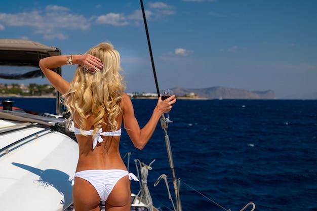 Woman in bikini tanning and relaxing drinking wine on a summer catamaran sailing cruise