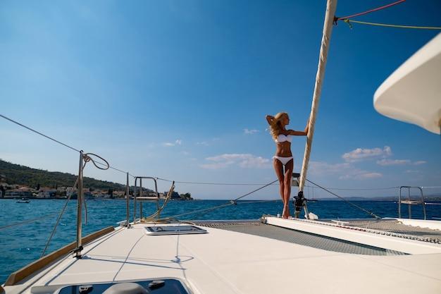 Woman in bikini tanning and relaxing on a summer catamaran sailing cruise