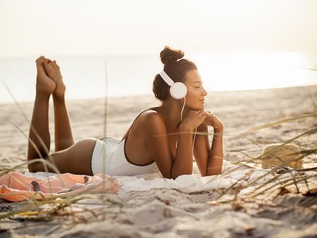 Woman in bikini with a smartphone and headphones on the beach