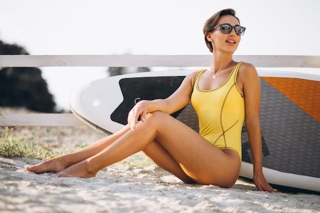 Woman in bikini with a surfing board at he beach