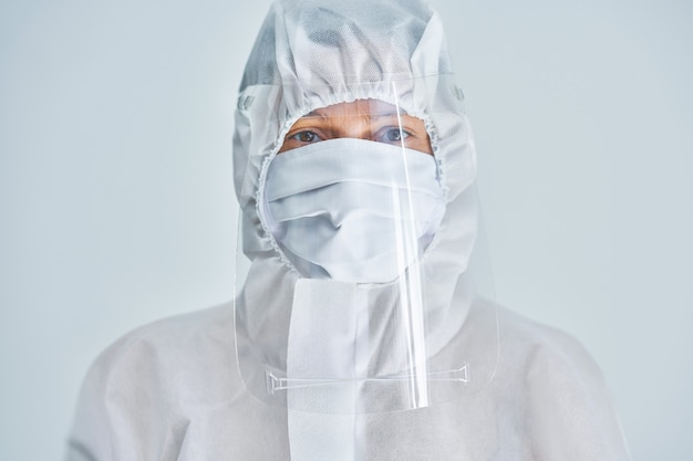 Woman in bio-hazard suit and face shield on white background.