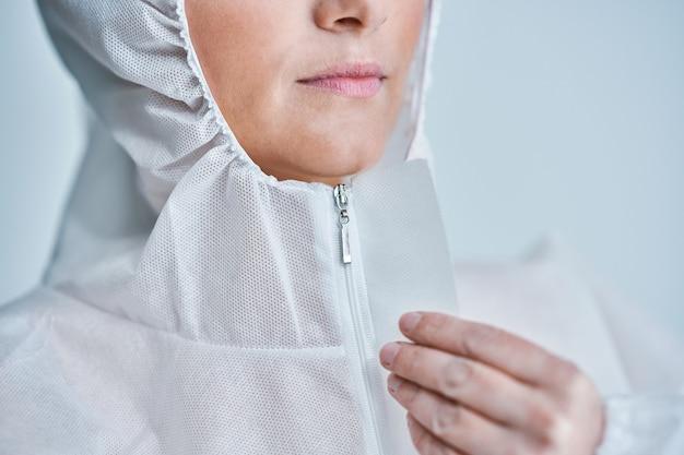 Woman in bio-hazard suit over white background.