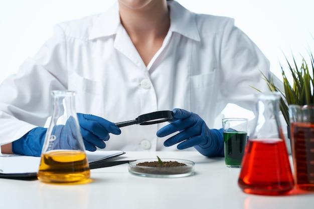 테이블 연구 공장에 앉아 여성 생물 학자 흰색 코트