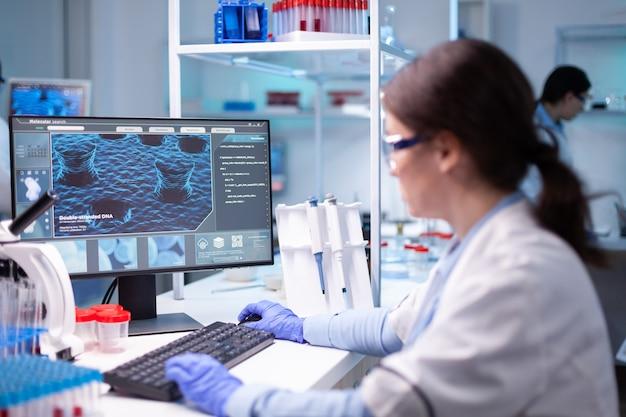 개발 실험실에서 연구하는 컴퓨터에서 일하는 여성 생명공학 과학자