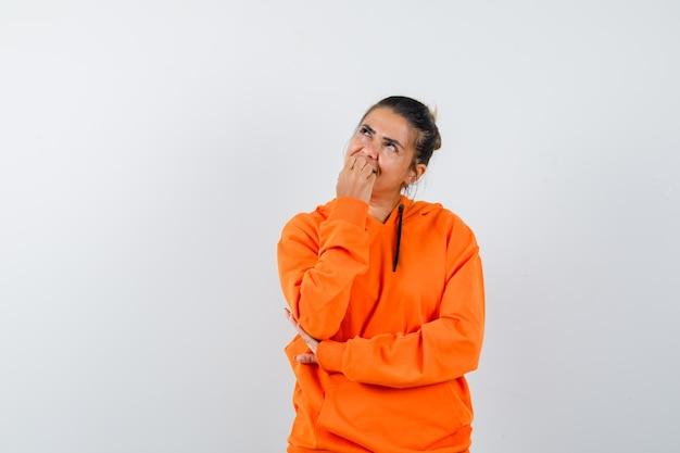 Женщина в оранжевой толстовке с капюшоном кусает ногти и выглядит мечтательно