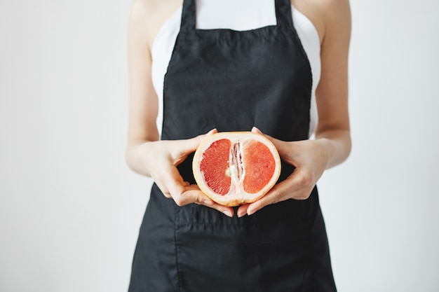 Woman in black apron holding half of grapefruit in hands over white wall. copy space.