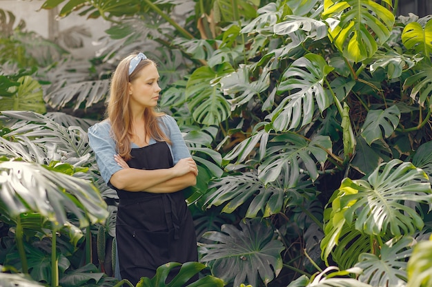 Woman in a black apron working in a greenhouse