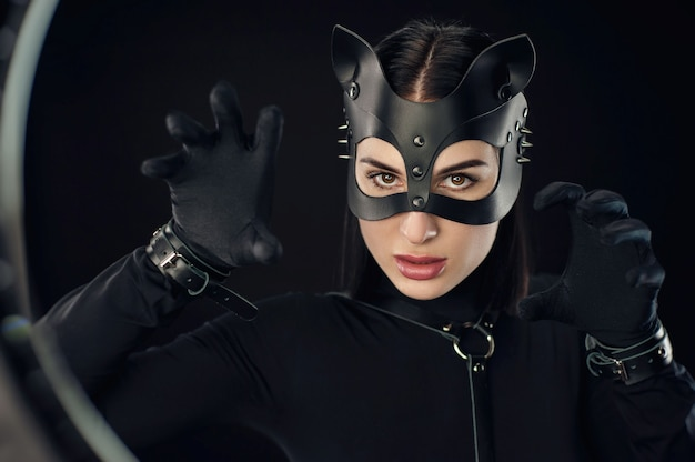 The woman in black belt and cat mask emotional portrait