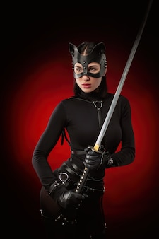 The woman in a black belt and cat mask with a katana