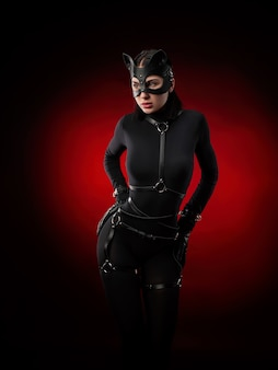 The woman in a black body belt and cat mask