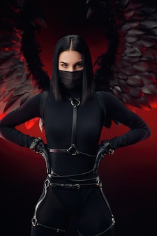 The woman in a black bodysuit with leather straps and black wings on a dark red background