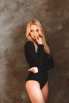 Woman in black bodysuit. woman with wavy hair. sensual gorgeous young lady in black bodysuit posing