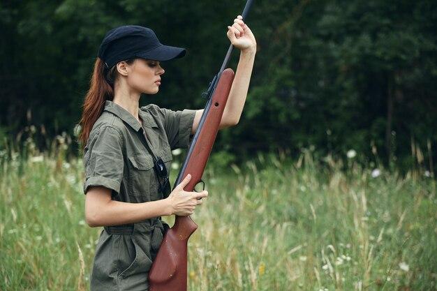 Женщина в черной кепке и зеленом комбинезоне держит в руках оружие