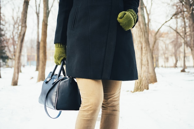 Woman in a black coat, green gloves and a bag walks in the park in winter