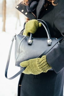 Woman in the black coat and green gloves holds a handbag close-up