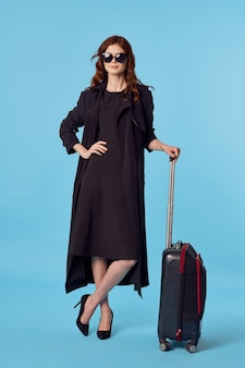 Woman in black coat luggage airport travel blue background business trip